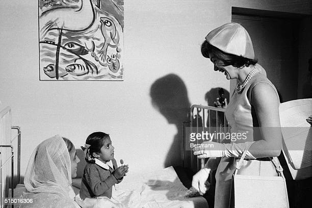 Mrs Jacqueline Kennedy smiles as a child samples a lollipop she has just given her at the all India Institute of Medical Sciences Mrs Kennedy was...