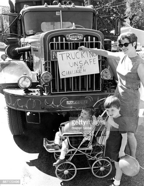 Mrs James Cummings holds a sign protesting gravel trucks with Christopher John and Jacquelin at Edgemere Road in the Roxbury neighborhood of Boston...