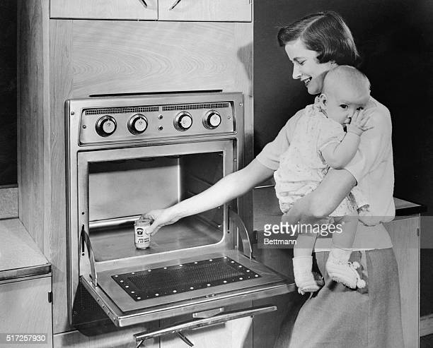 Mrs Joanne Meese of Mansfield Ohio holds her child as she prepares baby food in cool oven in 45 seconds by using the new electronic cooking unit for...