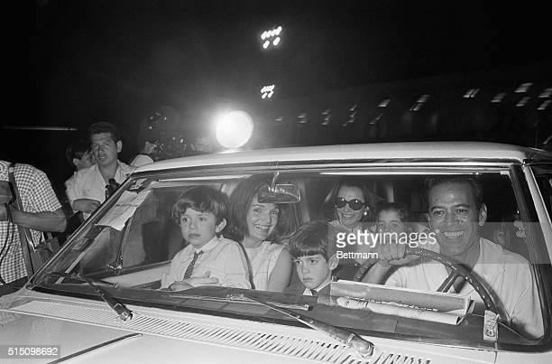 Mrs John F Kennedy and her sister princess Lee Radziwill sit in car with their children following their arrival at this jet set resort early March...