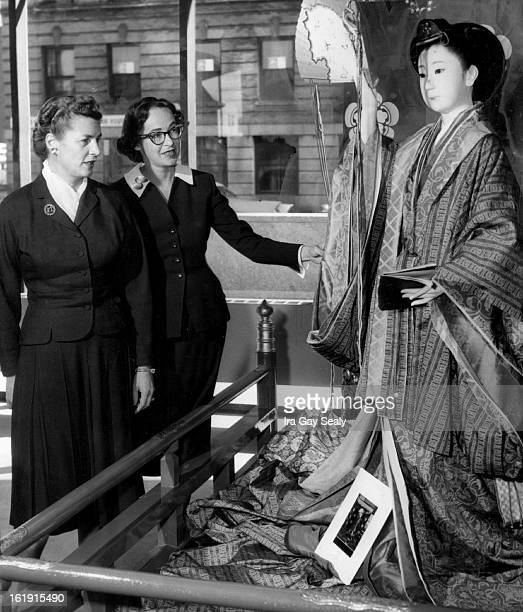 Mrs Jon Evans Jr. And Mrs. Frank Ashley inspect a Junihitoe, a 12-layer ceremonial robe, worn by the nobelwomen between the 7th and 12th centuries.;