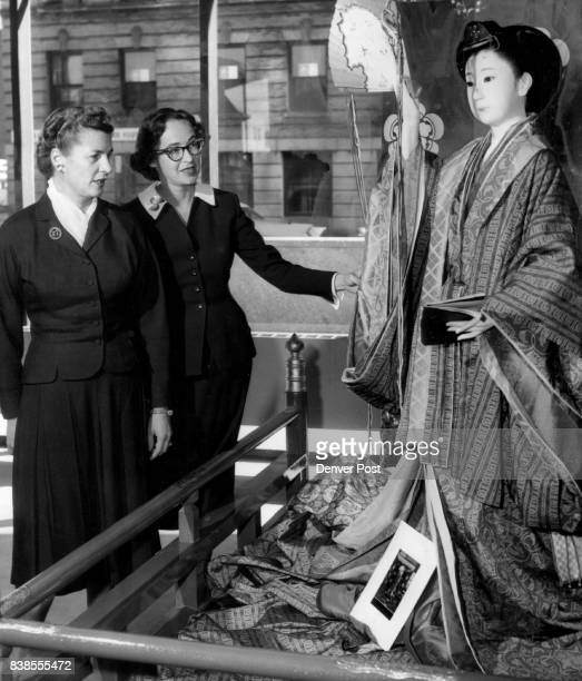 Mrs Jon Evans Jr. And Mrs. Frank Ashley inspect a Junihitoe, a 12-layer ceremonial robe, worn by the nobelwomen between the 7th and 12th centuries....