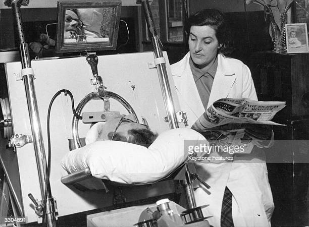 Mrs Kenneth Evans reads to her husband who is in an Iron Lung suffering from infantile paralysis in Mitcham Isolation Hospital
