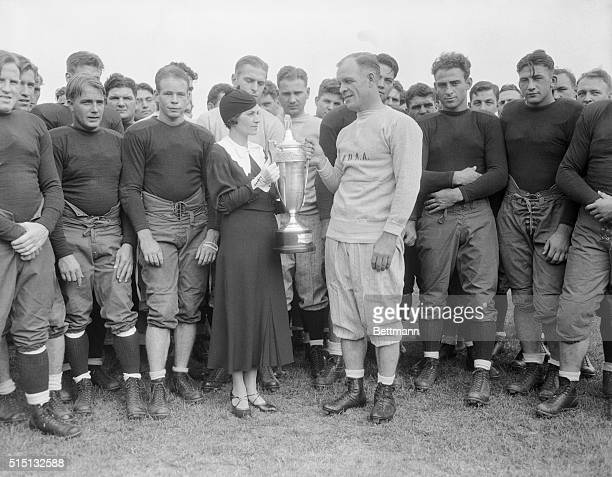 Mrs. Knute Rockne, the widow of the famous coach, is shown presenting the All American Captain's Cup for 1932 to Coach Hunk Anderson of Notre Dame...