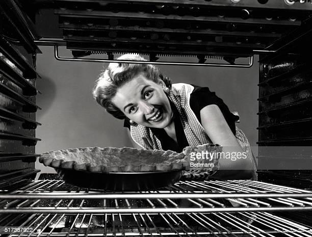 Mrs Krantz of Minneapolis beams at her apple pie baking in the oven in 1951