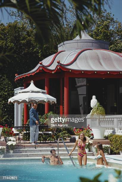 Mrs Lee Kinsolving descending the steps into the pool at Albin Holder's home Palm Beach Florida May 1970