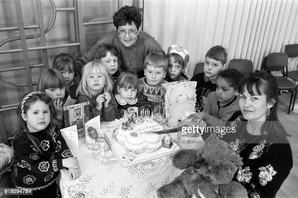 Mrs Lesley Holmes leader of St John's playgroup in Golcar is pictured with Mrs Catherine Nethercoats who made the birthday cake and the children...