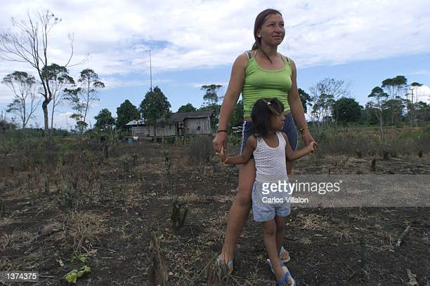 Mrs Lopez and her daughter stand in the backyard of their home August 31 2002 in the hamlet of Esmeraldas Colombia Lopez is one of several farmers in...