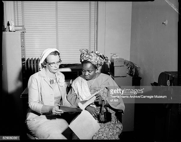Mrs Louis H Sweterlitsch and Queen Nurudden Adekogbe of Nigeria wearing African dress including gele or head scarf examining itinerary and seated in...