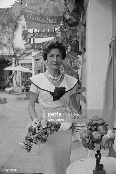 Mrs Loy Anderson stops at the Au Bon Gout boutique in an arcade off Worth Avenue Palm Beach Florida circa 1955 The Italian silk dress with sailor...