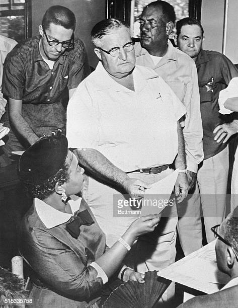 Mrs Mamie Bradley of Chicago is handed a subpoena by Sheriff H C Strider to testify in the trial of two white men charged with murdering her...