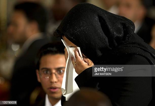 Mrs Mansura Shajahan covers her fave with a napkin as US President Barack Obama acknowledges her as he hosts an Iftar dinner celebrating Ramadan in...