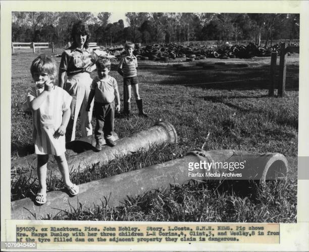 Mrs Marga Dunlop with her three children LR Corina Clint and Wesley 8 in from of the tyre filled dam on the adjusted property they claim in dangerous...