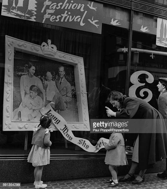 Mrs Marshall of Corstorthine shows her daughter Marion a portrait of the Royal Family on display in a department store shop window in preparation for...