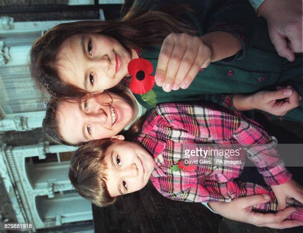 Mrs Maureen Roou and her children Adam and Poppy hold up a traditional red poppy outside their home in Islington north London today after objecting...