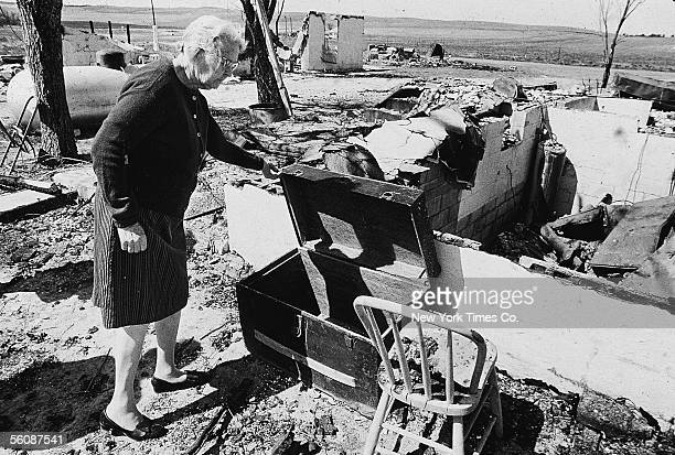 Mrs Orville Lansberry wife of the pastor fo the Church of God of Wounded Knee picks through the ruins of their home after the American Indian...