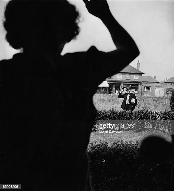 Mrs Pearce waves to her husband as he returns home from the coal mine with his working clothes under his arm Armthorpe near Doncaster UK August 1947