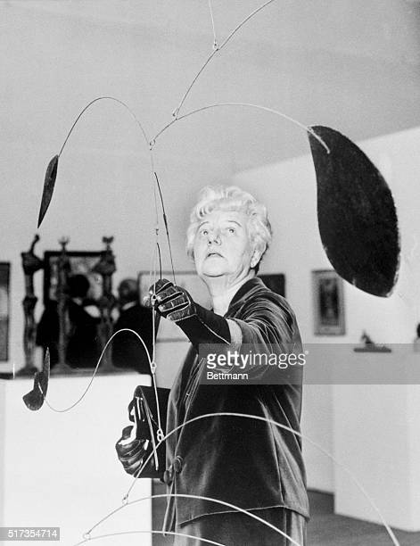 Mrs Peggy Guggenheim adjusts a mobile by sculptor Alexander Calder at a special exhibition of her famed collection at the Tate Gallery in London...
