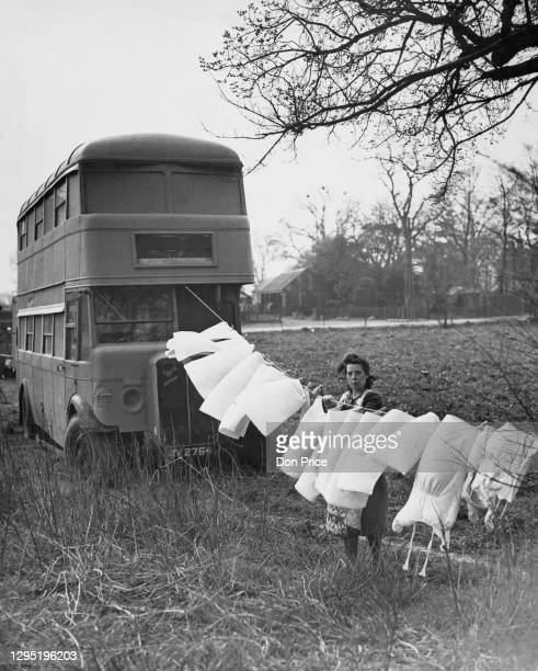 Mrs Prince hanging out the laundry on a washing line, which has one end attached to the double-decker bus which Mrs Prince and her family have made...