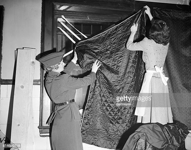 Mrs. R.A. Wetzler, an instructor with the American Women's Volunteer service, is demonstrating how to black out windows during WWII