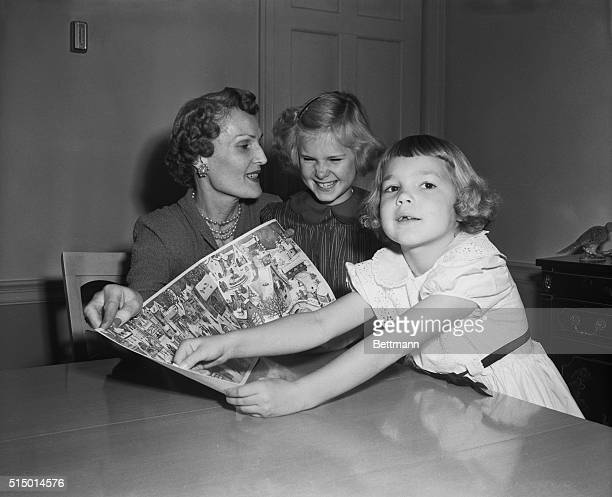Mrs Richard Nixon wife of Vice President Nixon is shown with their daughters Julie right and Patricia center as they look over a 'Little Christmas...