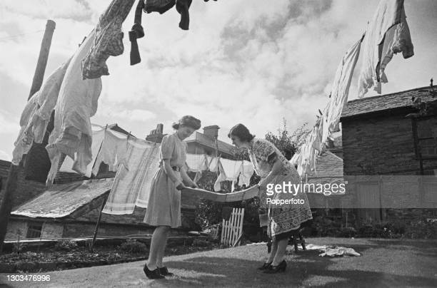 Mrs Rickard and a young girl fold up clothing from a washing line on washing day at her house in Liskeard, Cornwall, England during World War II on...