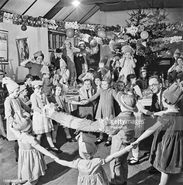 Mrs Rickard hosts a Christmas party for the twelve evacuee children she is looking after and evacuee friends in a festively decorated local hall in...