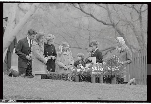 Mrs Robert F Kennedy together with five of her children and Senator and Mrs Edward Kennedy kneel at the grave of the late Senator Robert Kennedy in...