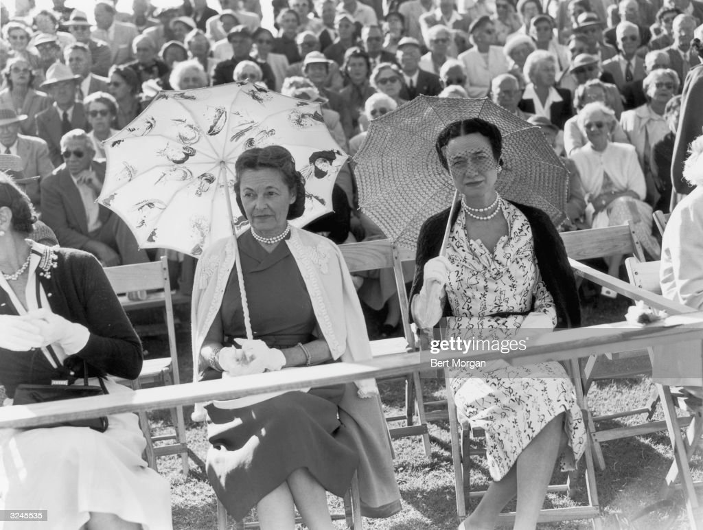 Mrs. Robert R. Young (left) and Wallis Simpson, the Duchess of Windsor, sit with parasols at a Gulf Stream polo match, Del Ray, Florida. The Duchess is wearing a pearls and a veil.
