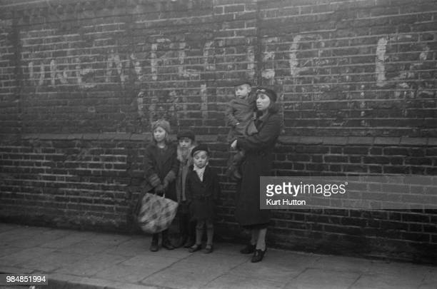 Mrs Smith waiting outside the Peckham Labour Exchange with her four children, for her husband, Albert Smith to collect his unemployment pay and to...