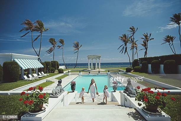 Mrs T Dennie Boardman and her children Samuel Jay and Sarah climbing the steps from the pool at the home of Boardman's parents in Palm Beach Florida...