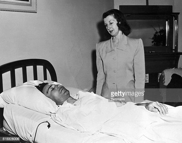 Mrs Valerie Hogan stands at the bedside of her husband pro golfer Ben Hogan as he rests in his hospital bed at El Paso Hogan was injured in an...
