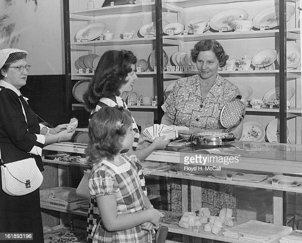 AUG 17 1953 AUG 20 1953 Mrs Violet A Wilkinson manager of the Columbine Premium store at 1725 Arapahoe street shows Mrs M S Conant and daughter...