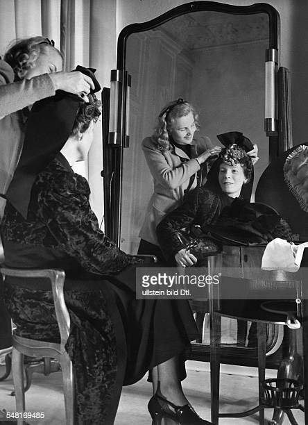 Mrs von Wülfing trying on a hat in the salon of Berlin modiste and hatter Madame Berthe 1941 Photographer Regine Relang Published by 'Die Dame'...