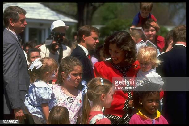 Mrs VP Marilyn Quayle holding crabbyfaced tot mingling w children enjoying WH Easter egg hunt