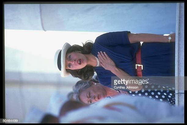 Mrs VP Marilyn Quayle poised w handoverheart sporting rakish straw hat singing Natl Anthem at Arlington Natl Cemetery Memorial Day ceremony
