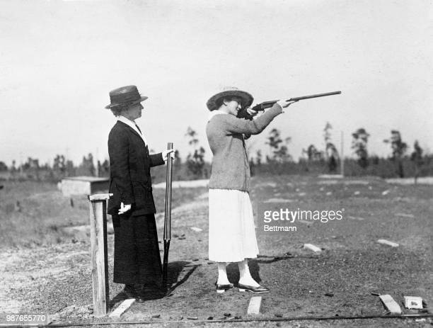 Mrs W Gould Brokaw shoots at flying targets At the left is Annie Oakley