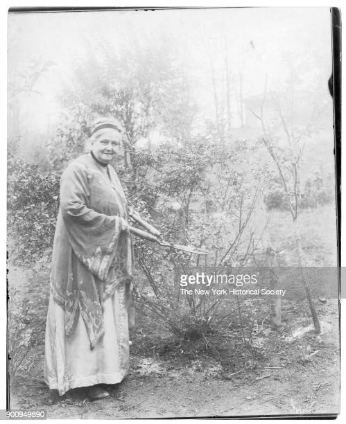 Mrs Wade in flowing tunic and headband with garden clippers next to tall shrub Ossining New York 1916