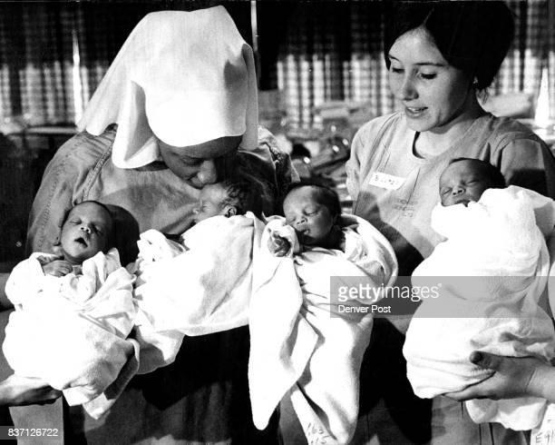 Mrs Wilber Tarver left and nurse Barbara Lutz hold the Tarver quadruplets born Dec 7 at Denver General Hospital just before Mrs Tarver took one of...