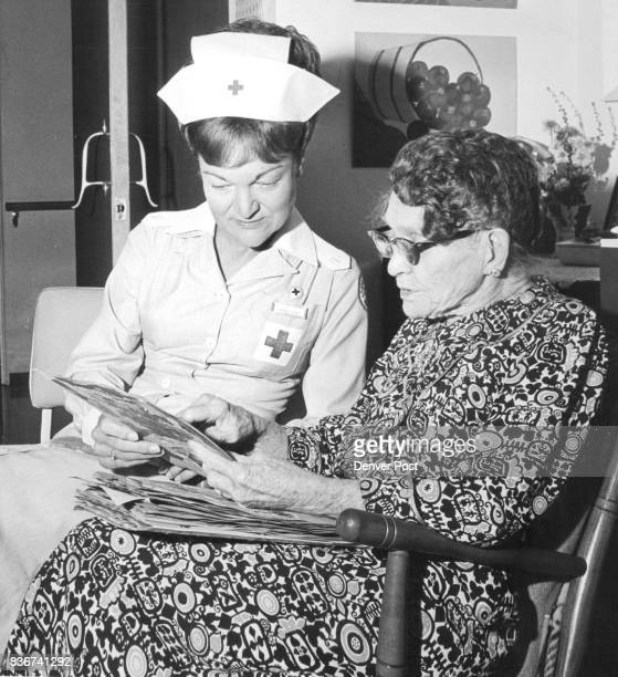 Mrs William B Young Jefferson County volunteers chairman goes over a scrapbook with Mrs Laura Cholewa patient at Casa Del Nursing home Credit Denver...