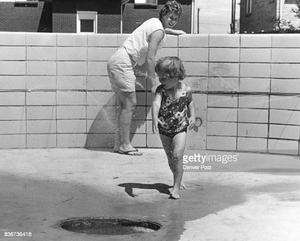 Mrs William Tooley of 5430 Estes St Arvada pushes the button in the spray pool and her daughter Janell runs away from the jets of water Credit Denver...