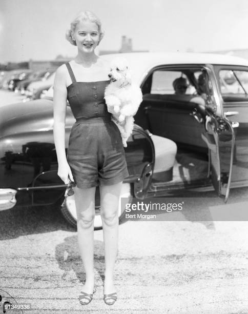 Mrs Winston Guest holding a poodle under her arm in front of a parked car in Southampton NY c1953