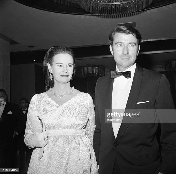 Mrs Wyatt Cooper better known as Gloria Vanderbilt peeks over the shoulder of her husband and gives the cameraman a big smile as she arrives at the...