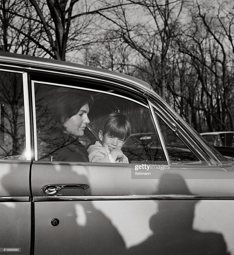 Mrs.John F. Kennedy and her son, John Jr., leave by automobile after delivering the former First Lady's daughter Caroline to the British Embassy, where the young lady attends school. The Kennedys returned to Washington from an 18 day holiday stay in Florida.