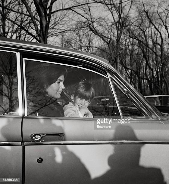 MrsJohn F Kennedy and her son John Jr leave by automobile after delivering the former First Lady's daughter Caroline to the British Embassy where the...