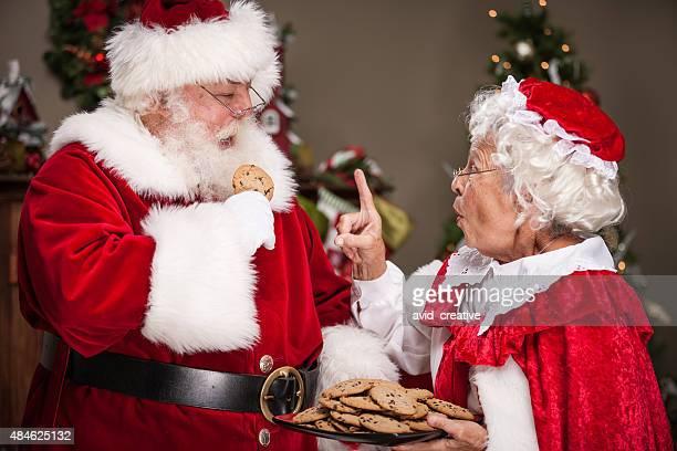 frau weihnachtsmann scolds santa claus zum essen zu viele cookies - weihnachtsfrau stock-fotos und bilder