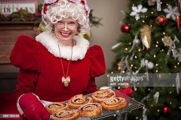 frau weihnachtsmann mit zimtbrötchen - weihnachtsfrau stock-fotos und bilder