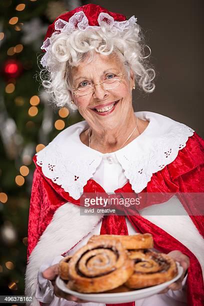 frau weihnachtsmann mit teller zimtbrötchen - weihnachtsfrau stock-fotos und bilder