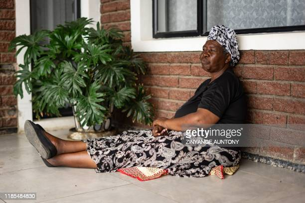 Ms Elina Dzingire sit outside the West Memorial Clinic after treatment in the Cowdray Park township, Bulawayo, in Zimbabwe on November 22, 2019. -...