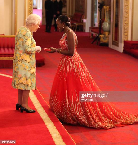 Ms Elizabeth Kasujja from Uganda receives her Young Leaders Award from Queen Elizabeth II during the Queen's Young Leaders Awards Ceremony at...